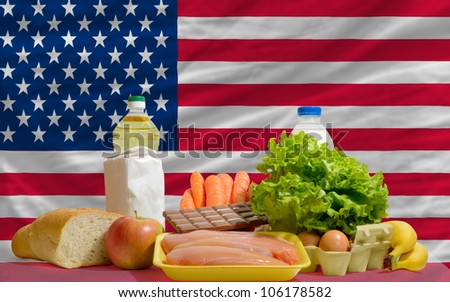 complete national flag of us covers whole frame, waved, crunched and very natural looking. In front plan are fundamental food ingredients for consumers, symbolizing consumerism - stock photo
