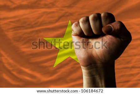 complete national flag of vietnam covers whole frame, waved, crunched and very natural looking. In front plan is clenched fist symbolizing determination - stock photo