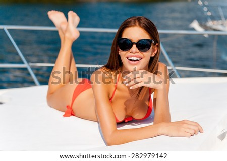Complete relaxation. Cheerful young woman in red bikini holding hand on chin and smiling at camera while lying on the deck of yacht  - stock photo