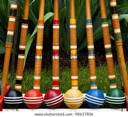Complete set of croquet mallets and balls on grass - stock photo
