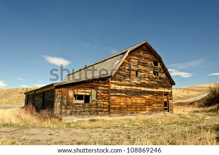 Completed in 1910 as a community hall for a small Montana town, this is the only remaining building.  It was built to look like a barn because agriculture was the main industry in the area. - stock photo