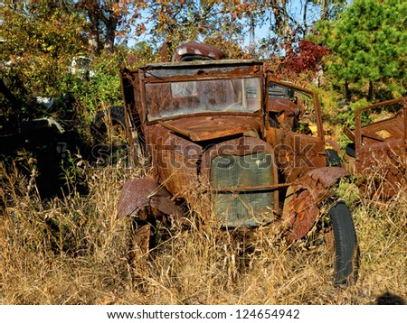 Completely rusted early Model T Ford rusting in the sun and the woods - stock photo