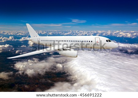 Completely white passenger Jet airplane. Aircraft is flying high in the blue cloudy sky. - stock photo