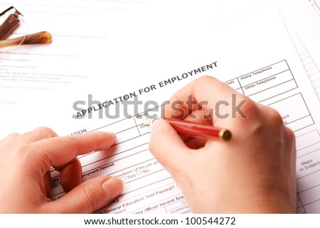 Completing an employment application.Glasses in the background - stock photo