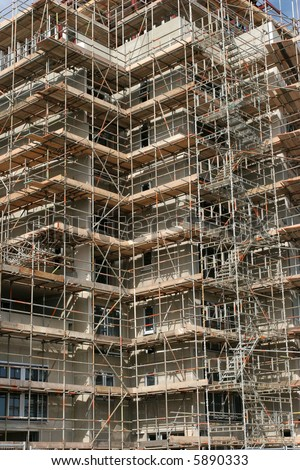Complex scaffolding on a new skyscraper under building construction.