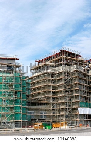 Complex scaffolding on new skyscrapers under building construction. - stock photo