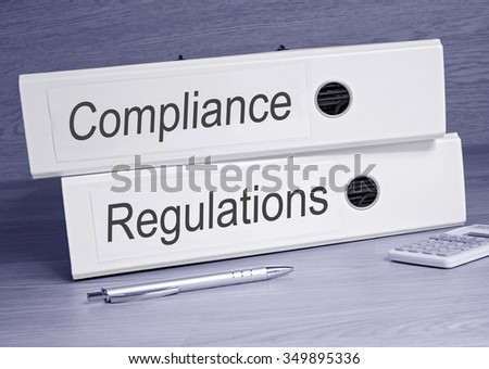 Compliance and Regulations - two binders on desk in the office with pen and calculator
