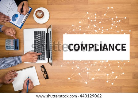 COMPLIANCE Business team hands at work with financial reports and a laptop - stock photo