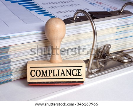 Compliance - rubber stamp with binder and paper in the office  - stock photo