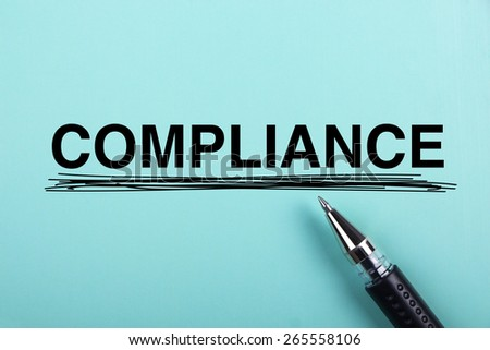 Compliance text is on blue paper with black ball-point pen aside. - stock photo