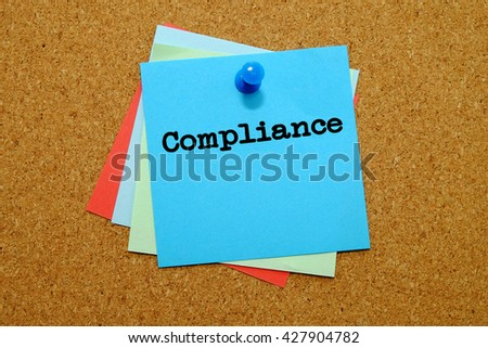 Compliance written on colored sticker notes over cork board background. - stock photo
