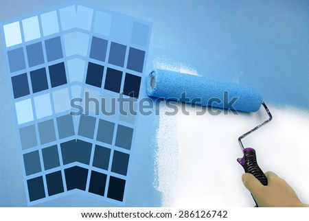 complimentary blue color chart and hand painting wall - stock photo