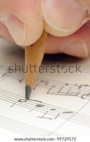 composing musical notes, writing a song with a pencil on paper - stock photo