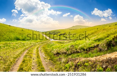 composite highland landscape. with pine forest far away near the road through hillside meadow in morning light with rainbow - stock photo
