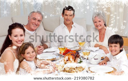 Composite image of a Family having a dinner together at home against fir tree forest and snowflakes - stock photo