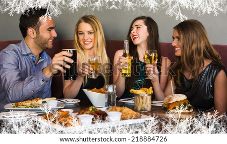 Composite image of a Friends having dinner together and toasting against snow - stock photo