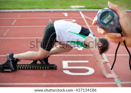 Composite image of a hand holding a timer against athletic man on the starting line putting his foot in the starting block - stock photo