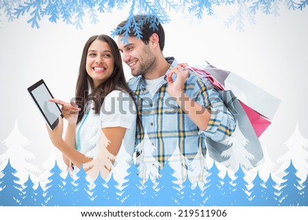 Composite image of Attractive young couple with shopping bags and tablet pc with frost and fir trees - stock photo