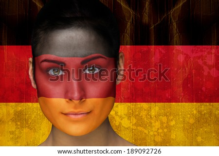 Composite image of beautiful football fan in face paint against germany flag in grunge effect