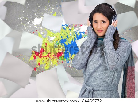 Composite image of beautiful model wearing knitted pullover and scarf listening to music