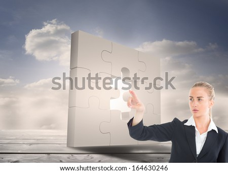 Composite image of blonde businesswoman pointing somewhere