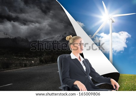 Composite image of blonde businesswoman sitting on swivel chair in black suit
