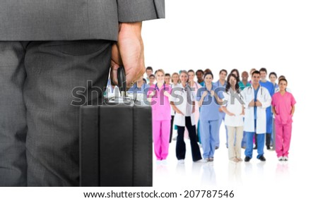 Composite image of businessman holding briefcase against group of workers - stock photo