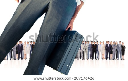 Composite image of businessman holding briefcase against row of business people - stock photo