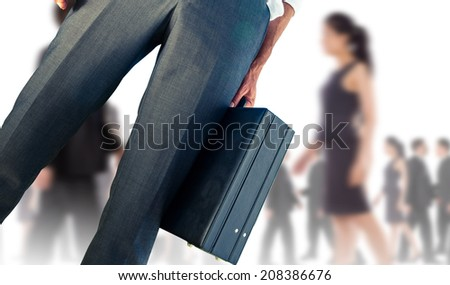 Composite image of businessman holding briefcase against silhouettes of business people