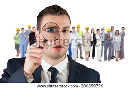 Composite image of businessman looking through magnifying glass against group of workers - stock photo