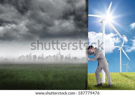 Composite image of businessman pushing away scene of city on the horizon - stock photo