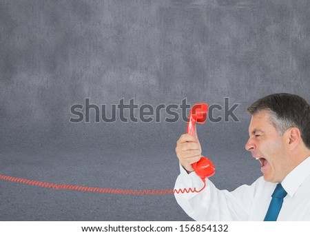 Composite image of businessman screaming directly into the handset on grey background - stock photo