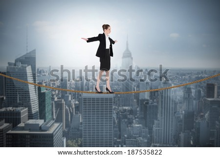 Composite image of businesswoman performing a balancing act against cityscape - stock photo