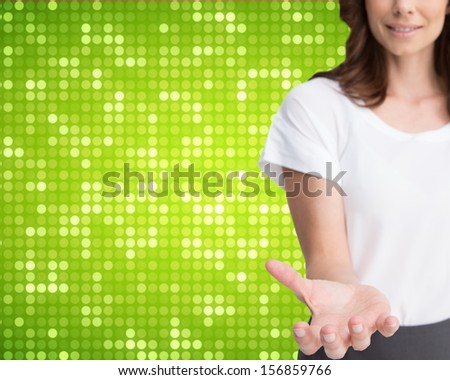 Composite image of businesswoman presenting her empty hand on green dotted background - stock photo