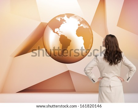 Composite image of businesswoman standing back to camera with hands on hips  - stock photo