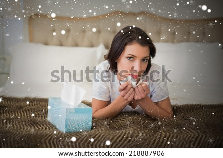 Composite image of calm pretty brown haired woman sneezing in a tissue against snow - stock photo
