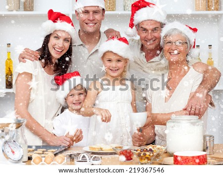 Composite image of Children baking Christmas cakes in the kitchen with their family with snow - stock photo