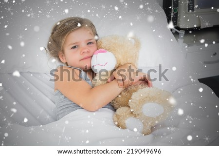 Composite image of cute girl embracing teddy bear in hospital bed against snow falling