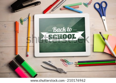 Composite image of digital tablet on students desk showing back to school message - stock photo