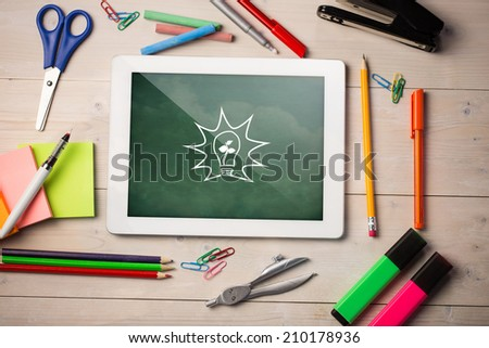 Composite image of digital tablet on students desk showing light bulb - stock photo