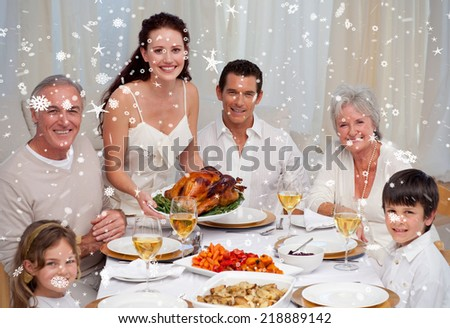 Composite image of Family eating turkey in a dinner against snow falling - stock photo