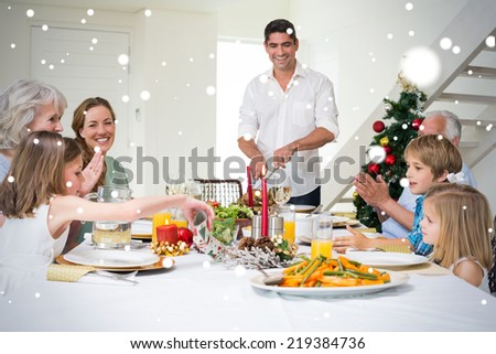 Composite image of Family enjoying Christmas meal at dining table against snow - stock photo