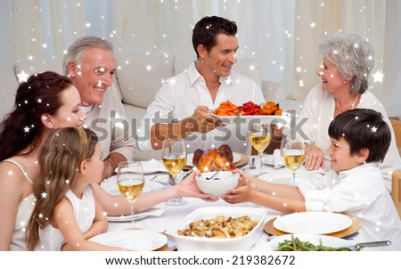 Composite image of Family having a big dinner at home against snow - stock photo