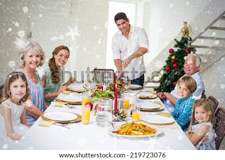 Composite image of Family having Christmas meal at dining table against snow - stock photo