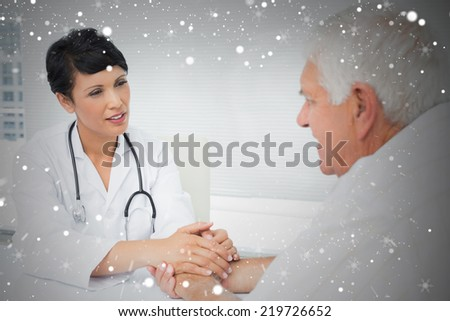 Composite image of female doctor holding senior patients hands against snow - stock photo