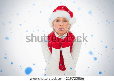 Composite image of festive woman blowing a kiss against snow falling - stock photo