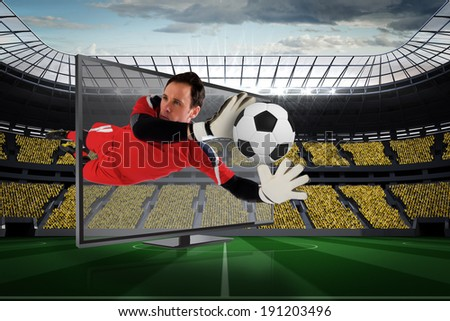 Composite image of fit goal keeper saving goal through tv against vast football stadium with fans in yellow - stock photo