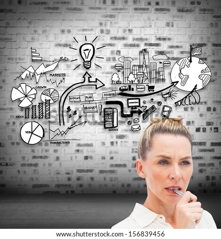 Composite image of focused businesswoman with pen on mouth in front of economic illustration - stock photo