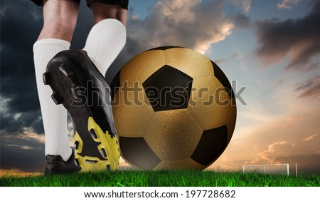Composite image of football boot kicking huge gold ball against green grass under blue and orange sky