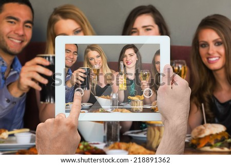Composite image of hand holding tablet pc showing photograph - stock photo